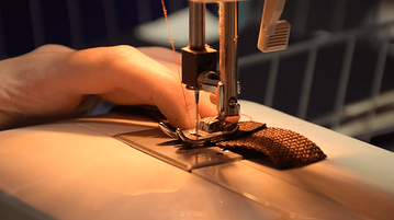 Cosplayer sewing elastic to woven nylon for armor straps