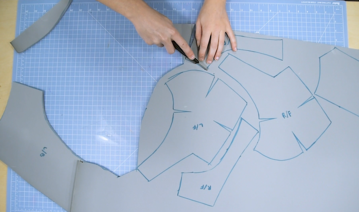 Cosplayer cutting out foam pattern pieces for armor